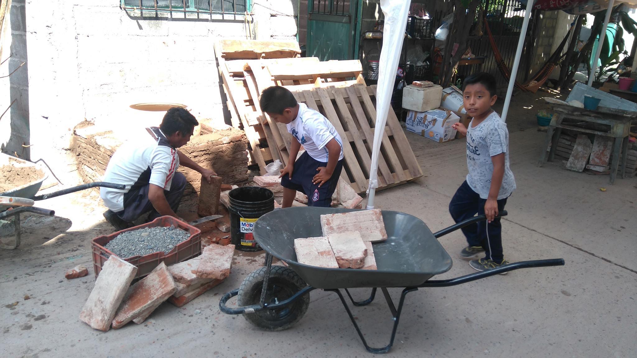 los niños del escuadrón hormiguita ayudando a la colocación de un horno de comixcal